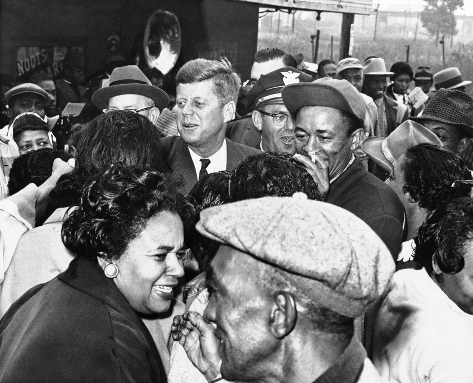 Sen. John F. Kennedy greets residents of the all African American community of Brooklyn, a suburb of East St. Louis, during campaign tour of Southern Illinois, Oct. 3, 1960 in St. Louis, Ill. The democratic presidential nominee and not scheduled a stop there but when he noticed a crowd had turned out with a brass band, he stopped anyway and greeted many of them personally. (AP Photo/Bob Scott)